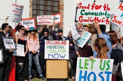 Mestni svet Santa Monice je maja prepovedal oddajanje celotnih stanovanj za manj kot 30 dni. Protesti, kakršen je na fotografiji, torej niso bili učinkoviti. Na njem so zagovorniki Airbnbja pozivali: »Pustite nas, da gostimo«, »Sprejmite pošteno in napredno zakonodajo zdaj«, »Z delitvijo sem rešil svoj dom« …